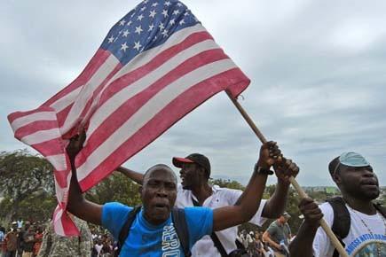 Des Haïtiens brandissent un drapeau américain et chantent... (Photo: AFP)