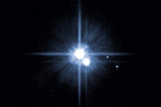 Pluton et ses trois lunes.... (Archives AFP)