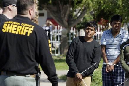 Des immigrants illégaux, les mains liées, escortés par... (Photo AP)