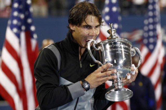 Rafael Nadal pose pour le photographes en croquant... (Photo: Reuters)