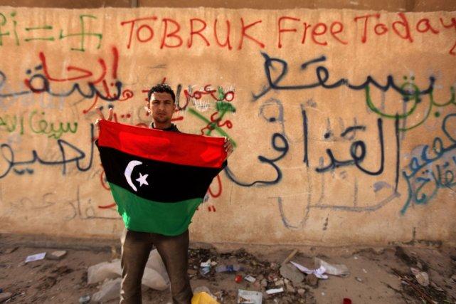 À Tobruk, un homme brandit le drapeau libyen... (Photo: AFP)