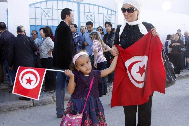 Une jeune fille tient un drapeau tunisien alors... (Photo: AFP)
