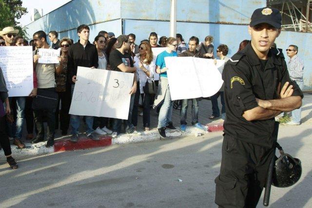 Un policier surveille des manifestants réunis hier à... (photo: Zoubeir Souissi, reuters)