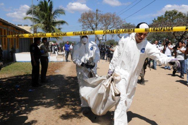Des techniciens médico-légaux transportent le corps d'une des... (Photo: Orlando Sierra, AFP)
