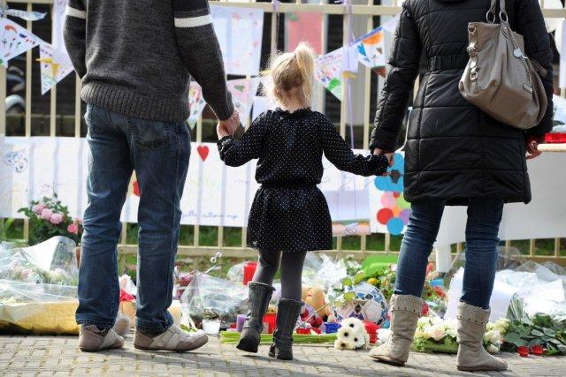 Une petite fille, accompagnée de ses parents, regarde... (Photo: Yorick Jansens, AFP)