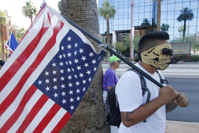 Un Hispanique, portant un masque de tête de... (Photo: Darryl Webb, Reuters)