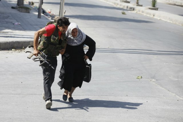 Un rebelle syrien aide une femme à traverser... (Photo Goran Tomasevic, Reuters)