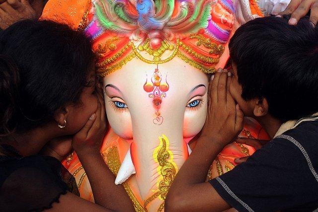 Des croyants hindous chuchotent leurs souhaits à Ganesh,... (Photo: AFP)