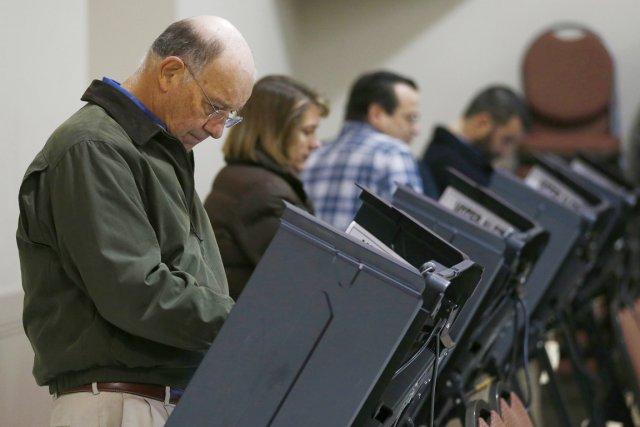 Des électeurs enregistrent leur vote dans une église... (PHOTO CHRIS KEANE, REUTERS)