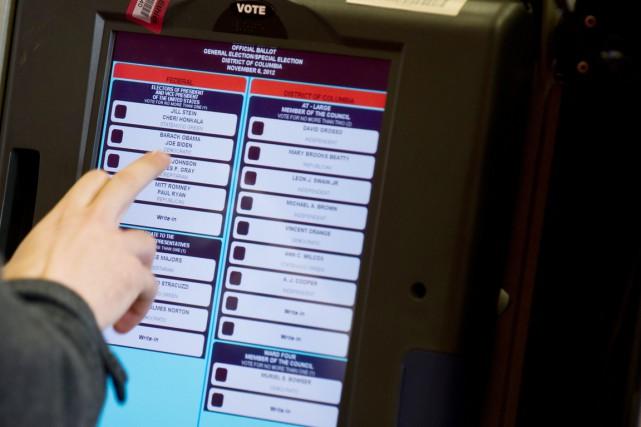 Un électeur vote à l'aide d'une mahcine électronique... (PHOTO NICHOLAS KAMM, AFP)
