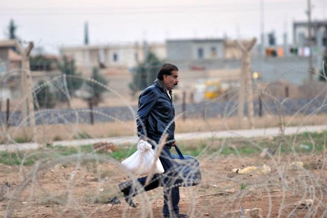 Un réfugié syrien s'apprête à traverser la frontière... (PHOTO AFP)