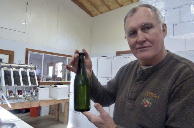 Chuck Shelton tient une bouteille du cidre qu'il... (FABIENNE FAUR)