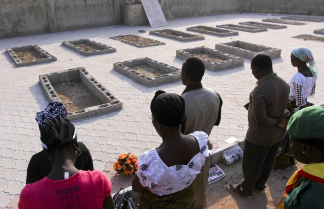 Des chrétiens prient sur les tombes de victimes... (PHOTO AFOLABI SOTUNDE, REUTERS)