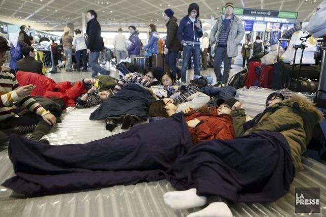Des voyageurs se reposent sur le sol à... (Photo: AP)