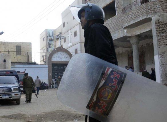 La police anti-émeutes monte la garde devant l'église... (Photo Ibrahim Zayed, AP)