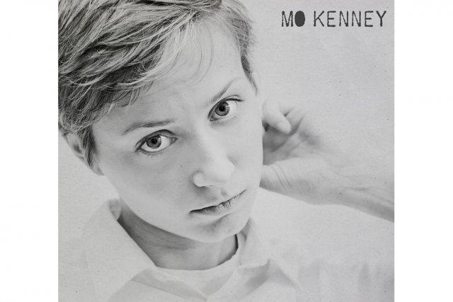 Cheveux courts à la garçonne, chemise pâle et veste noire, Mo Kenney affiche un...