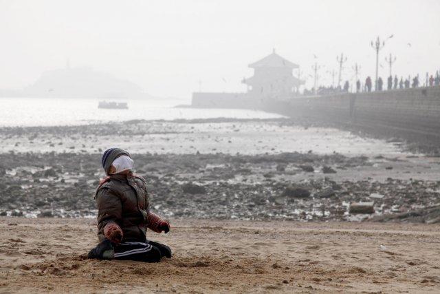 Un jeune garçon, portant un masque, joue sur... (PHOTO ARCHIVES AFP)