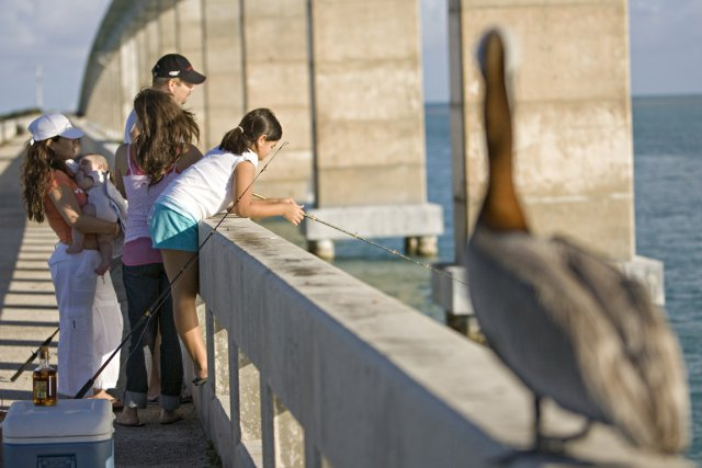 Une famille pêche sous le regard d'un pélican... (Photo David Boily, La Presse)
