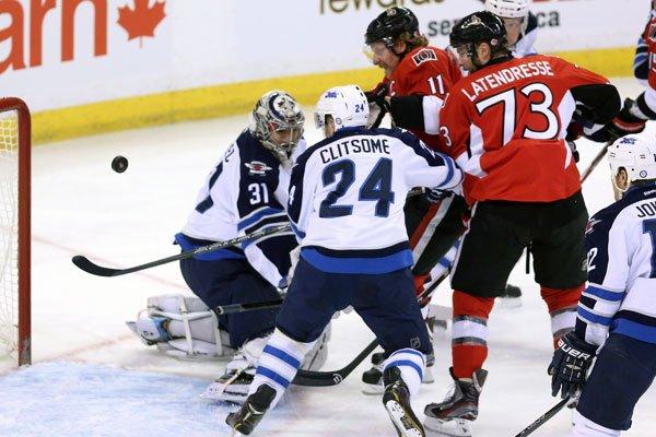 Daniel Alfredsson et Guillaume Latendresse regardent la rondelle... (La Presse Canadienne)