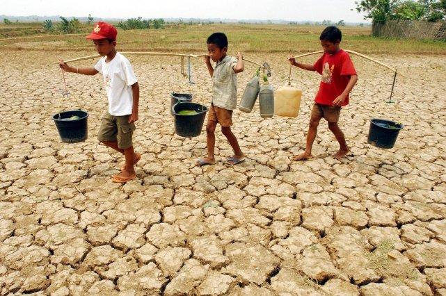 Trois garçons indonésiens transportent des seaux d'eau durant... (PHOTO ARCHIVES AFP)