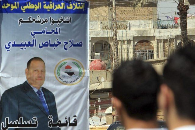 Des Iraquiens passent devant une bannière montrant le... (PHOTO ALI AL-SAADI, AFP)