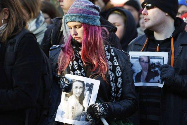 Des personnes tiennent dans leurs mains la photo... (Photo Paul Darrow, Reuters)