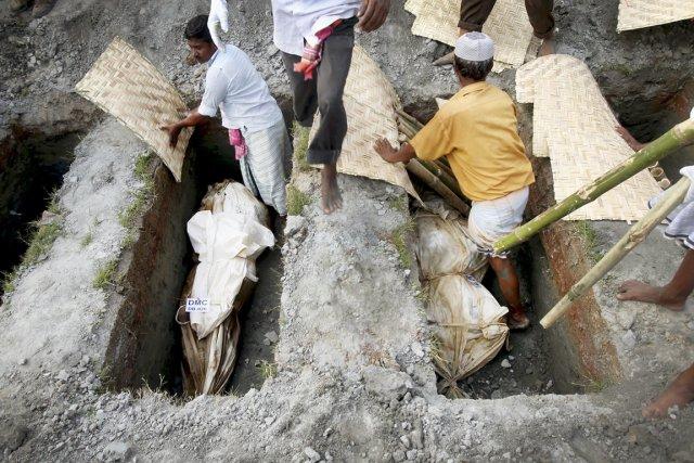 Des travailleurs enterrent des cadavres non réclamés, à... (PHOTO WONG MAYE-E, AP)