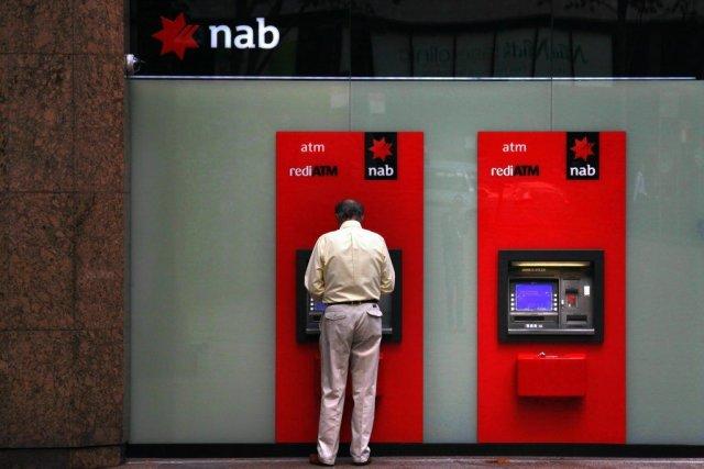 Un homme retire de l'argent d'un guichet automatique... (Photo Reuters)
