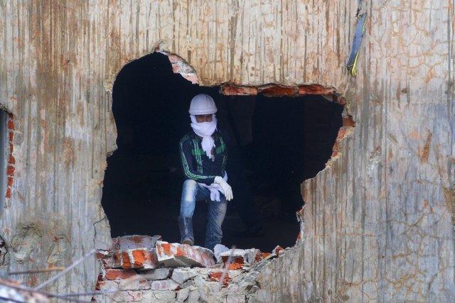 Un secouriste regarde à l'extérieur des ruines de... (Photo Ismail Ferdous, Associated Press)