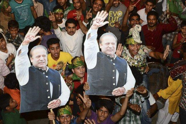 Des supporters tiennent des portraits du premier ministre... (Photo Arif Ali, AFP)