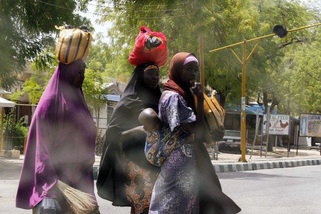 Des femmes traversent la rue avec leurs biens... (Photo: Reuters)