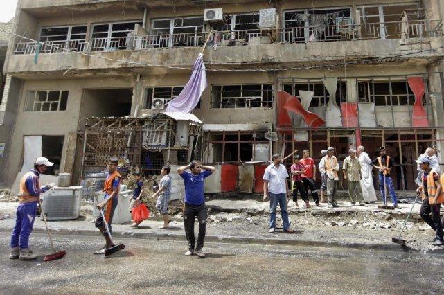 Des travailleurs municipaux de Bagdad nettoient des débris,... (Photo Khalid Mohammed, AP)