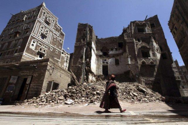 Une femme passe devant la façade d'une maison... (PHOTO MOHAMED AL-SAYAGHI, REUTERS)