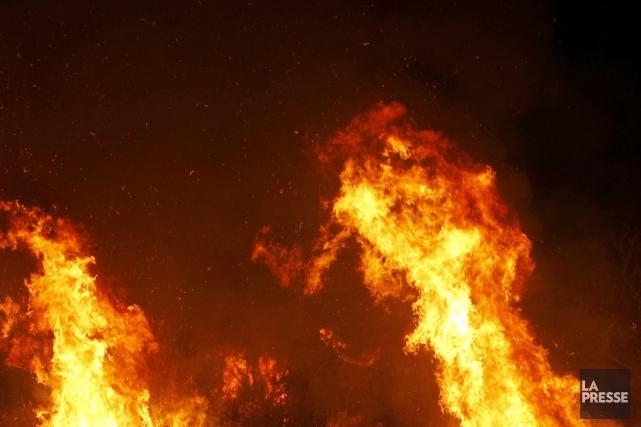 Des pompiers appelés à éteindre un incendie qui s'était déclaré dans une maison... (PHOTO ARCHIVES REUTERS)