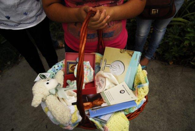 Une jeune fille tient un panier rempli d'items... (PHOTO ULISES RODRIGUEZ, REUTERS)