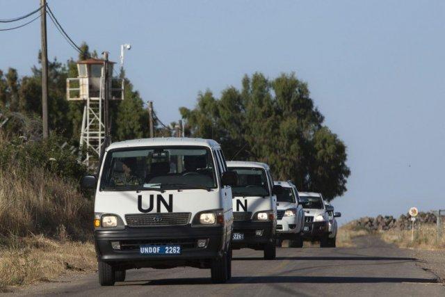 Les véhicules de l'ONU entrent dans une base... (Photo Sebastian Scheiner, AP)