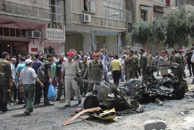 Des officiels inspectent la carcasse de la voiture... (PHOTO REUTERS)