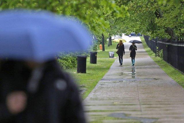 Des piétons sous la pluie au centre-ville de... (Photo Devaan Ingraham, La Presse Canadienne)