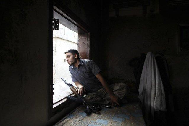 Un soldat rebelle monte la garde dans un... (PHOTO MUZAFFAR SALMAN, REUTERS)