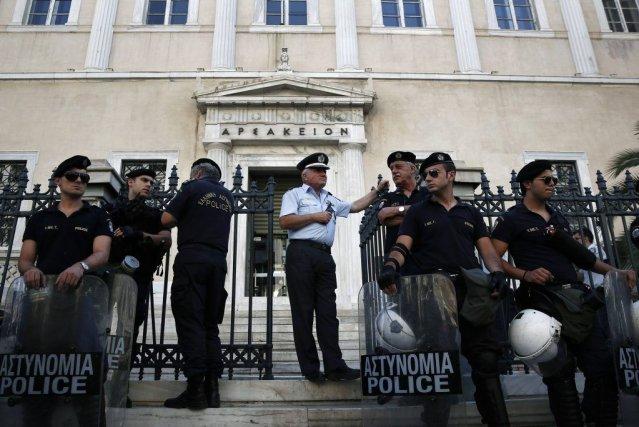 Des policiers montent la garde devant le Conseil... (PHOTO YORGOS KARAHALIS, REUTERS)