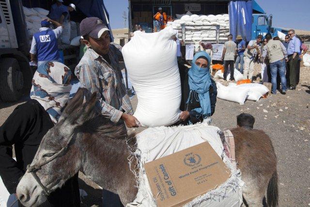 Des travailleurs du PAM distribuent des denrées alimentaires... (PHOTO AHMAD GHARABLI, AFP)