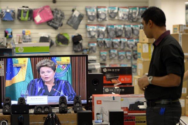 Un travailleurs écoute l'intervention de la présidente Dilma... (PHOTO YASUYOSHI CHIBA, AFP)