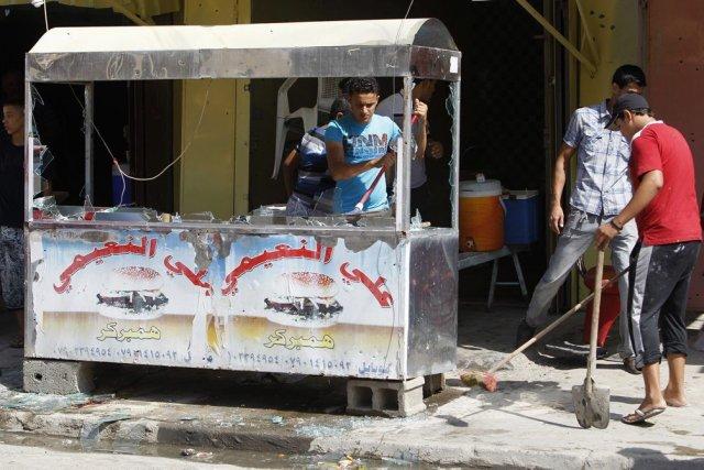 Des jeunes nettoient après l'explosion d'une bombe dans... (PHOTO SAAD SHALASH, REUTERS)