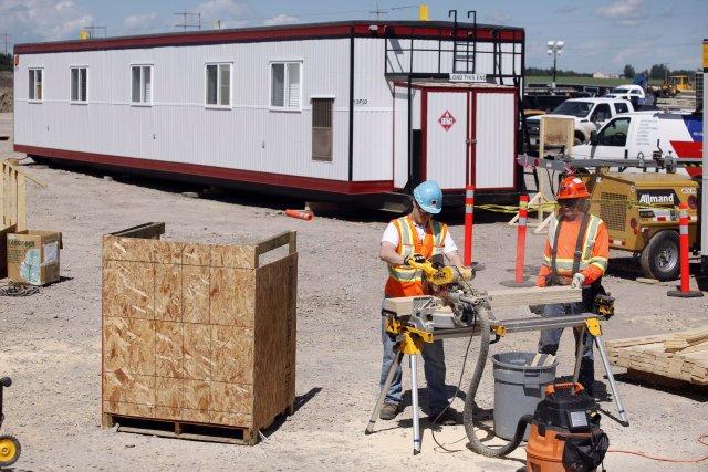Des ouvriers s'affairent à la reconstruction de la... (Photo Jeff McIntosh, La Presse Canadienne)