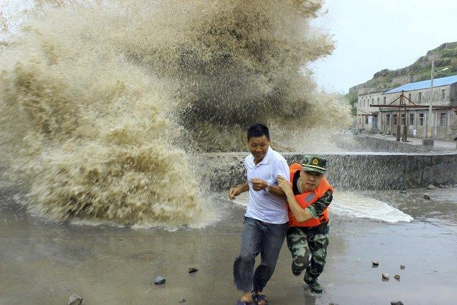 Un soldat chinois aide un homme à s'éloigner... (Photo: Reuters)