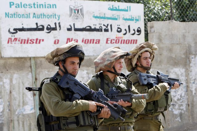 Trois soldats israéliens montent la garde d'ans une... (PHOTO MOHAMAD TOROKMAN, ARCHIVES REUTERS)