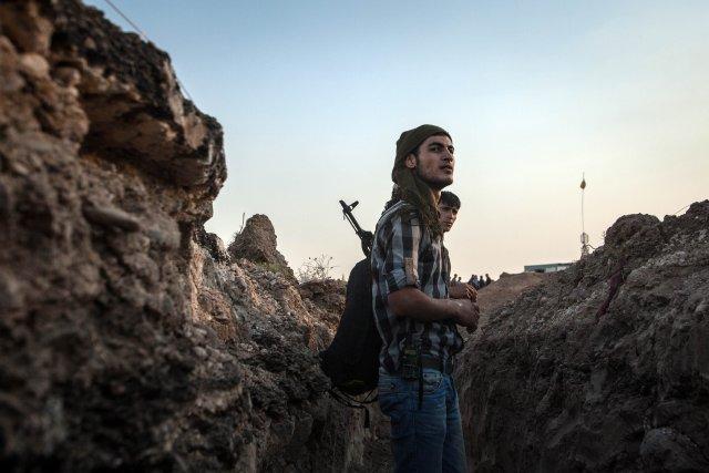 Des combattants kurdes tiennent leur position dans une... (PHOTO  ALICE MARTINS, AFP)