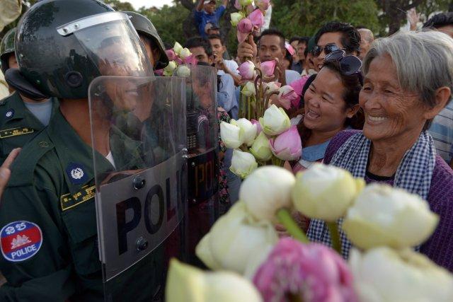 Les manifestants se promenaient, lotus à la main.... (Photo TANG CHHIN SOTHY, AFP)