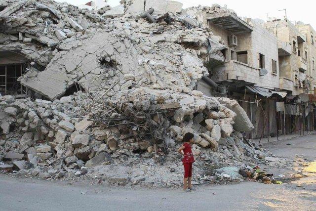 Une jeune Syrienne se tient devant des ruines... (Photo Reuters)