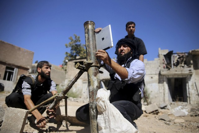 Un rebelle syrien consulte un iPad avant de... (Photo: archives Reuters)